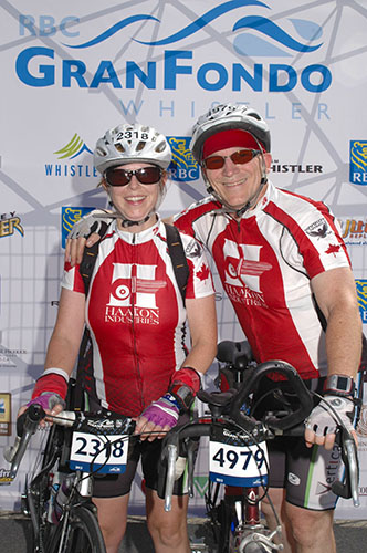 Rider Dave Vis poses with his wife in front of an RBC GranFondo Whistler banner