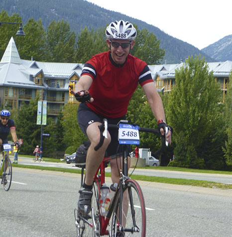 Michael Green smiling as he's about to cross the finish line in Whistler