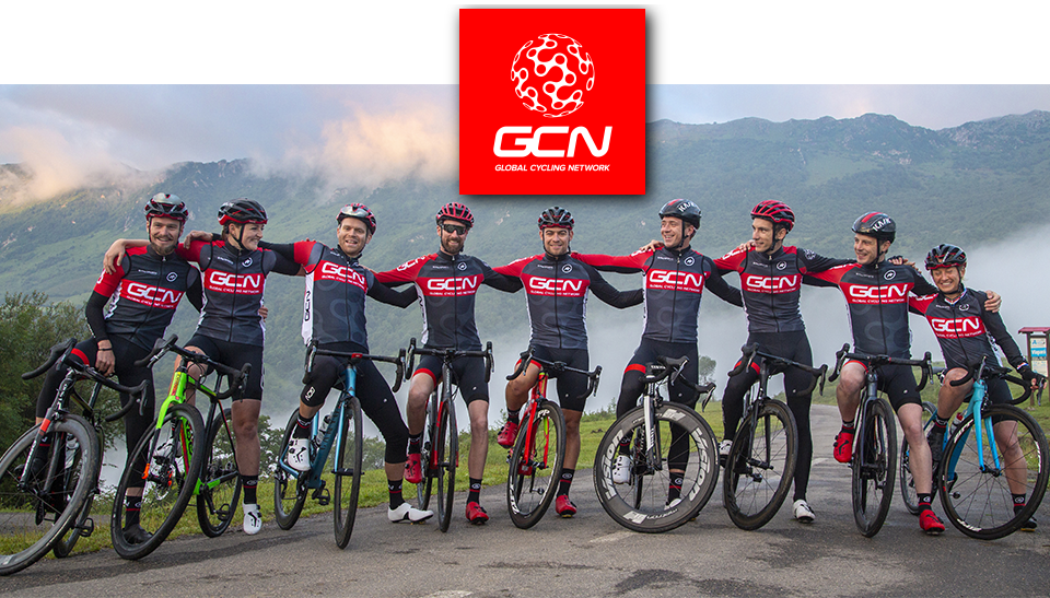 GCN's team pose with their bikes in front of a mountain scene