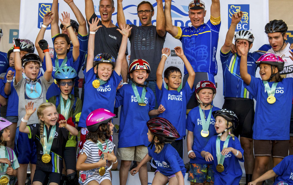 Kids celebrate on stage after receiving a cheque to support youth cycling